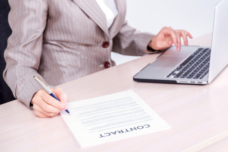 doings: Signing a business contract. Businessman sitting at the table and typing a business plan on a laptop while businessman sitting at desk on isolated gray background