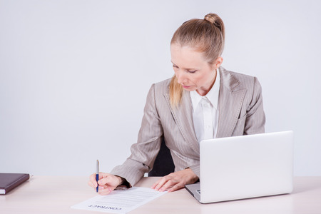 Signing a business contract. Woman Businessman sitting at the table and typing a business plan on a laptop while businessman sitting at desk on isolated gray background