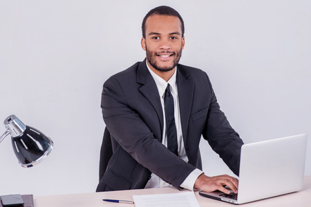 doings: Office worker. Smiling African businessman sitting at the table and typing a business plan on a laptop while a businessman sitting at a desk and smiling at the camera isolated on a gray background Stock Photo