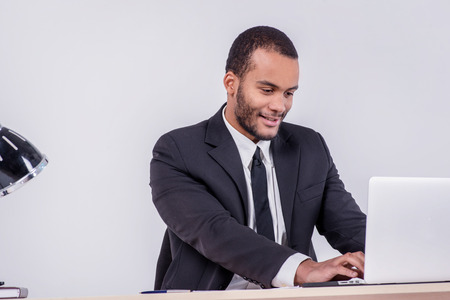 courteous: Courteous businesswoman. Smiling African businessman sitting at the table and typing a business plan on a laptop while a businessman sitting at a desk and smiling at the camera isolated on a gray background Stock Photo