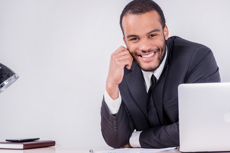Joyful businessman. Smiling African businessman sitting at the table and typing a business plan on a laptop while a businessman sitting at a desk and smiling at the camera isolated on a gray background photo