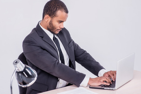 Work laptop. Smiling African businessman sitting at the table and typing a business plan on a laptop while a businessman sitting at a desk and smiling at the camera isolated on a gray background photo