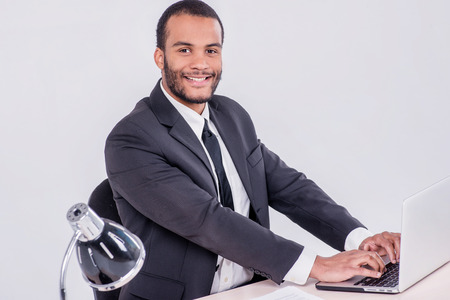doings: The successful operation. Smiling African businessman sitting at the table and typing a business plan on a laptop while a businessman sitting at a desk and smiling at the camera isolated on a gray background
