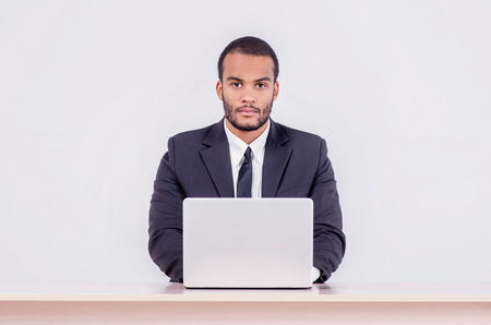 doings: Confident worker business. Smiling African businessman sitting at the table and typing a business plan on a laptop while a businessman sitting at a desk and smiling at the camera isolated on a gray background