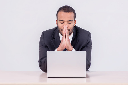 doings: Prayer at work. Smiling African businessman sitting at a desk on a laptop while a businessman sitting at a table and  holding his hands behind his head on isolated gray background