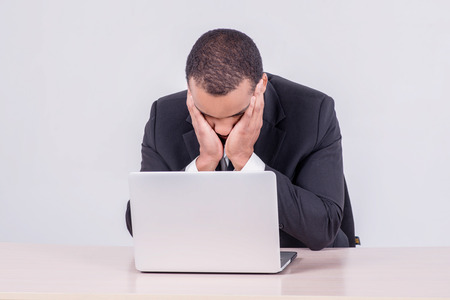 Tired businessman. Smiling African businessman sitting at a desk on a laptop while a businessman sitting at a table and holding his hands over face isolated on gray background photo