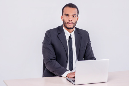Surprised businessman. Smiling African businessman sitting at a desk on a laptop while a businessman sitting at a table and holding hands on the laptop isolated on a gray background