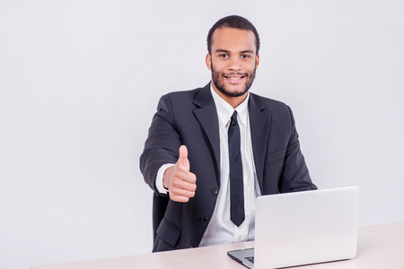 Smiling businessman. Smiling African businessman sitting at a desk on a laptop while a businessman sitting at a table and holding a thumb up over a laptop isolated on a gray background photo