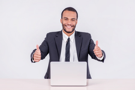 doings: Happy businessman. Smiling African businessman sitting at a desk on a laptop while a businessman sitting at a table and holding a thumb up over a laptop isolated on a gray background Stock Photo