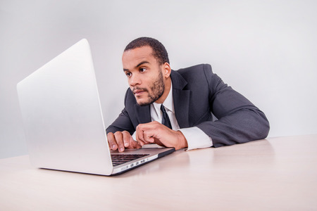 doings: Portrait of a businessman. Smiling African businessman sitting at a desk on a laptop while a businessman sitting at a desk and is actively working on a laptop isolated on a gray background