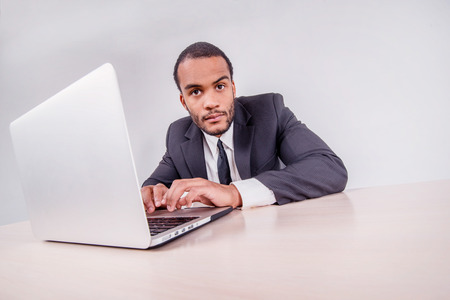 Portrait of a businessman. Smiling African businessman sitting at a desk on a laptop while a businessman sitting at a desk and is actively working on a laptop isolated on a gray background