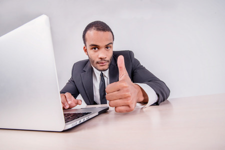 Good luck to you. Smiling African businessman sitting at a desk on a laptop while businessman sitting at the table and showing thumb up over a laptop isolated on a gray background photo