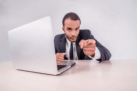 doings: Good luck to you. Smiling African businessman sitting at a desk on a laptop while businessman sitting at the table and shows an index finger upwards over a laptop isolated on a gray background Stock Photo