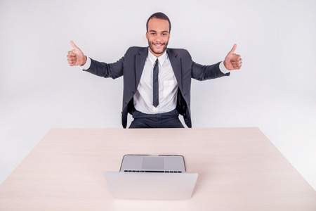 Successful work. Smiling African businessman sitting at a desk on a laptop while businessman sitting at the table and showing thumb up over a laptop isolated on a gray background photo