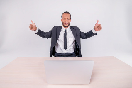 doings: Serious businessman. Smiling African businessman sitting at a desk on a laptop while businessman sitting at the table and showing thumb up over a laptop isolated on a gray background Stock Photo