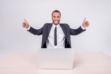 doings: successful businessman. Smiling African businessman sitting at a desk on a laptop while businessman sitting at the table and showing thumb up over a laptop isolated on a gray background Stock Photo