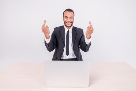 doings: Smiling businessman. Smiling African businessman sitting at a desk on a laptop while businessman sitting at the table and showing middle finger thumbs up over a laptop isolated on a gray background Stock Photo