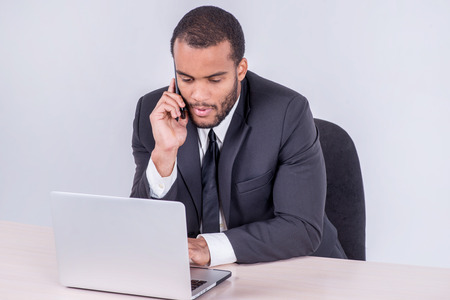 doings: Conversation with the client. Smiling African businessman sitting at desk talking on a cell phone while businessman sitting at the table and working on a laptop isolated on a gray background