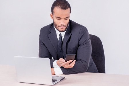 Call waiting customer. Smiling African businessman sitting at a desk and talking on a cell phone while businessman sitting at the table and working on a laptop isolated on a gray background