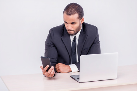Customer call. Smiling African businessman sitting at a desk and looking at mobile phone while businessman sitting at the table and working on a laptop isolated on a gray background photo