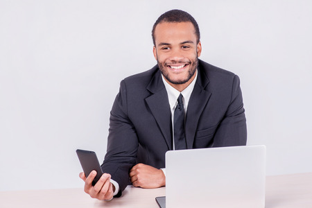 doings: Cell communication in the business. Smiling African businessman sitting at a desk and looking at mobile phone while businessman sitting at the table and working on a laptop isolated on gray background