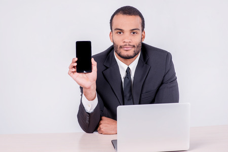 doings: Mobile phone and businessman. Smiling African businessman sitting at a desk and looking at mobile phone while businessman sitting at the table and working on a laptop isolated on a gray background Stock Photo