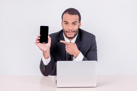 doings: Smiling African businessman sitting at the table and pointing at a mobile phone while businessman sitting at the table and working on a laptop isolated on a gray background