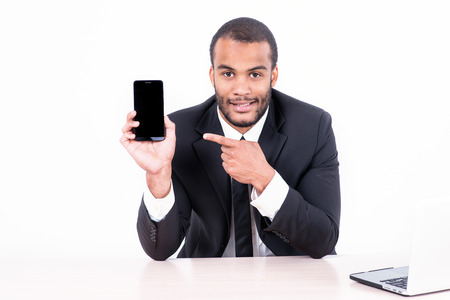 doings: Happy african businessman sitting at the table and pointing at a mobile phone while businessman sitting at the table and working on a laptop isolated on a gray background Stock Photo