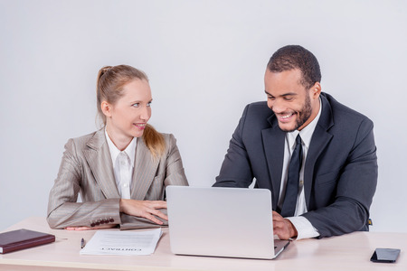 Successful teamwork. Two businessmen talking together while businessmen sitting at a table working on a laptop isolated on a gray background photo
