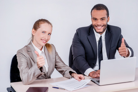 Best day to work together. Two smiling businessman looking at each other while businessmen sitting at a table working on a laptop showing a thumbs up on a gray background.