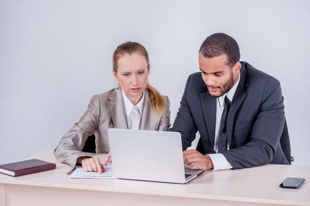 doings: Teambuilding. Two smiling businessman looking at each other while businessmen sitting at a table working on a laptop on a gray background.