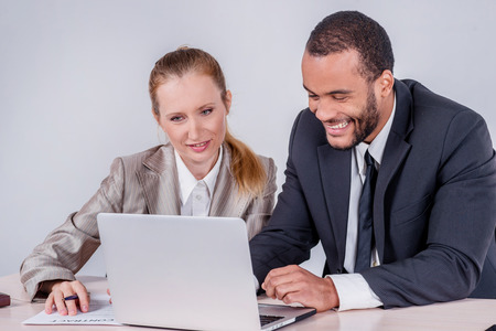 doings: New business objectives. Two smiling businessman looking at laptop while businessmen sitting at a table working on a laptop on a gray background.