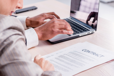 doings: Signing a business contract. Two successful businessman smiling and looking at the laptop while businessmen sitting at a table working on a laptop on a gray background close-up view.