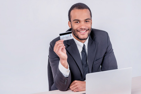 doings: Online sales. Successful African businessman sitting at a laptop and holding credit card in hand until businessman doing orders through the Internet