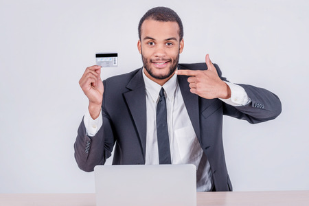 Internet banking. Successful African businessman sitting at a laptop and holding credit card in hand until businessman doing orders through the Internet photo