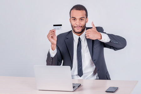 Purchase by credit card. Successful African businessman sitting at a laptop and holding credit card in hand until businessman doing orders through the Internet photo