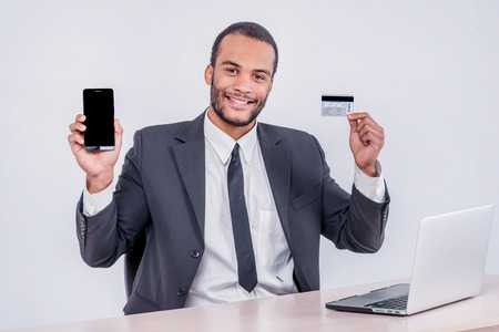 Internet banking for business. Successful African businessman sitting at a laptop and holding credit card in hand until businessman doing orders through the Internet photo