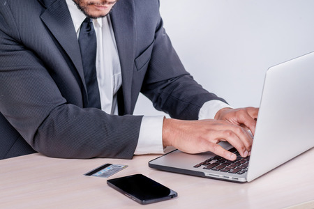 doings: Internet banking for business. Successful African businessman sitting at a laptop and holding credit card in hand until businessman doing orders through the Internet Stock Photo
