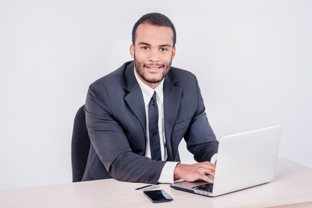 Internet banking for business. Successful African businessman sitting at a laptop and holding credit card in hand until businessman doing orders through the Internet Stock Photo