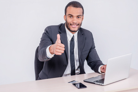 doings: Internet banking for business. Successful African businessman sitting at a laptop and holding credit card in hand until businessman doing orders through the Internet showing a thumbs up Stock Photo