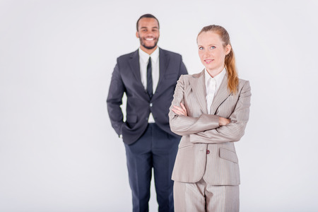 doings: Successful business people. Two confident and successful businessman standing with hands clasped while waiting customer on isolated gray background