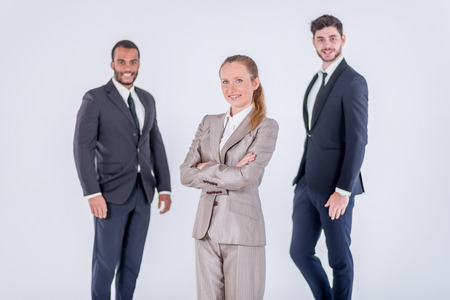Successful colleagues. Three confident and successful businessman standing with hands clasped while waiting customer on isolated gray background