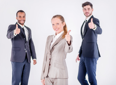 doings: Successful business day. Three confident and successful businessman standing with hands clasped while businessman showing a thumbs up on a gray background