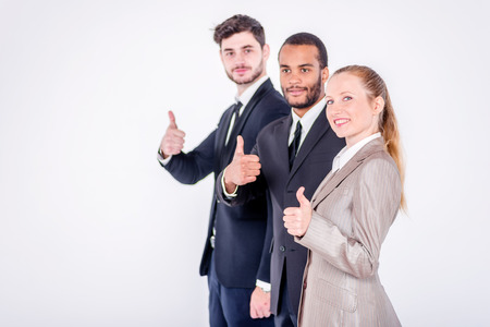 doings: The best employees. Three confident and successful businessman standing in a row while businessman showing a thumbs up on a gray background Stock Photo