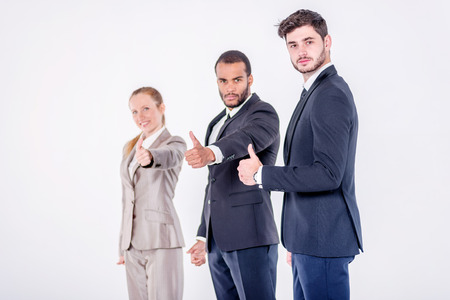 doings: Best business dealings. Three confident and successful businessman standing in a row while businessman showing a thumbs up on a gray background
