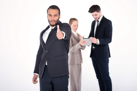 doings: Confident businessman. Successful African businessman standing and shows his thumb up while his colleagues are working on a tablet in the background on a gray background Stock Photo