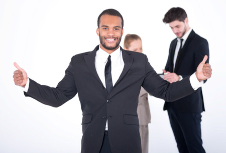 doings: Successful businessman. Successful African businessman standing and shows his thumb up throwing up his hands while his colleagues are working on a tablet in the background on a gray background