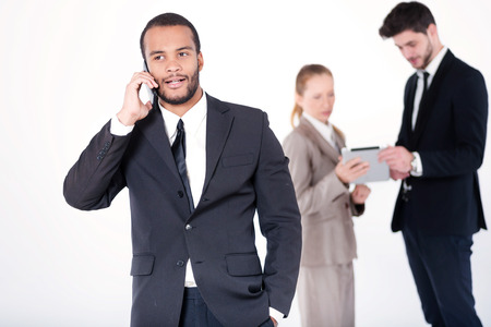 doings: Customer call. Successful and smiling African businessman talking on cell phone while his colleagues are working on a tablet in the background on a gray background