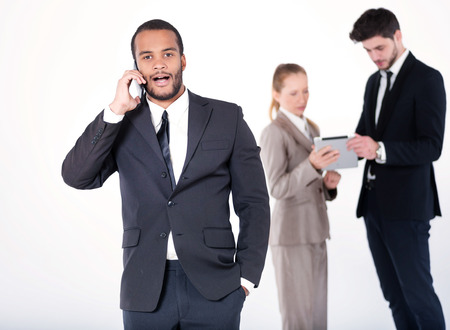 doings: Serious business conversation. Successful and smiling African businessman talking on cell phone while his colleagues are working on a tablet in the background on a gray background Stock Photo