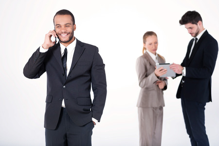 Cheerful business conversation. Successful and smiling African businessman talking on cell phone while his colleagues are working on a tablet in the background on a gray background photo